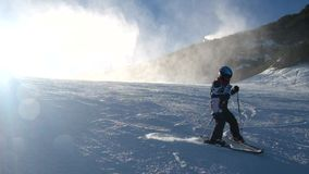 Snow making on slope. Skier near a snow cannon making fresh powder snow. Mountain ski resort in winter calm. Stock Image