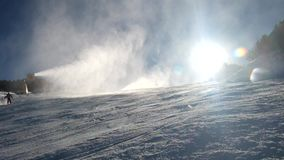 Snow making on slope. Skier near a snow cannon making fresh powder snow. Mountain ski resort in winter calm. stock video