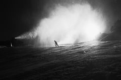 Snow making on slope. Skier near a snow cannon making fresh powder snow. Mountain ski resort in winter calm. Royalty Free Stock Photos