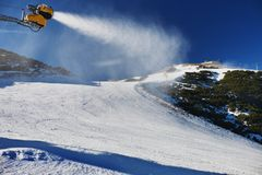 Snow making on slope. Skier near a snow cannon making fresh powder snow. Mountain ski resort in winter calm. Stock Photography