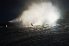 Snow making on slope. Skier near a snow cannon making fresh powder snow. Mountain ski resort in winter calm. Stock Photo