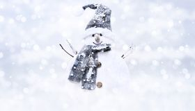 Snow man on blurred bright christmas lights background, greeting