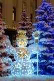 Snow man decorated with garland Royalty Free Stock Photos