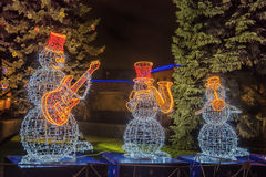 Snow man decorated with garland Royalty Free Stock Images