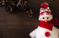 Snow man and pine cones. Christmas decoration of a snowman with a hat and a red scarf next to some pine cones on a wood background Stock Image