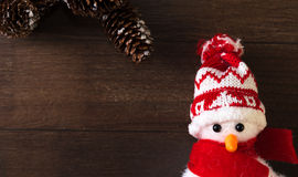 Snow man and pine cones. Christmas decoration of a snowman with a hat and a red scarf on a wood background Royalty Free Stock Photography