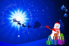 Snow man is pointing towards sleigh on blue back Stock Photography