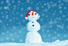 Snow man and snowflakes. Snow man in santa cap on nature in sunny cold day and snowflakes Royalty Free Stock Image