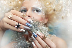 Snow manicure. Snow manicure on colored nail Polish with silver snowflakes on the girl Stock Photo