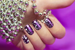 Snow manicure. Snow manicure with the design of the white crumbs on violet brilliant varnish for the nails royalty free stock images