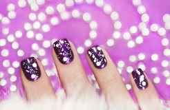Snow manicure. Snow manicure with the design of the white crumbs on violet brilliant varnish for the nails royalty free stock photos
