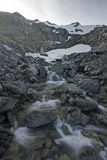 Snow melt. Clear mountain stream forms from summer snow melt from the rugged rocky peak of Bear Mountain on Baranof Island in southeast Alaska Royalty Free Stock Photography