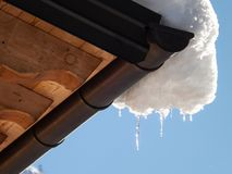 Snow melt down from roof. Sunny day and snow melt down from wooden roof royalty free stock photo
