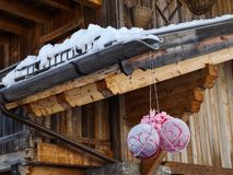 Snow melt down from roof. Sunny day and snow melt down from wooden roof an down frozen christmas balls royalty free stock photos