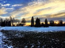 Snow Melt at Sunset in City Park. Evening sunset with recent snowfall melting on the ground in a city park in Denver, Colorado with trees scattered around. Large royalty free stock photos