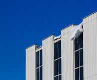 Snow meltdown. Snow melting from the roof of a building is great threat to people passing by Stock Photo