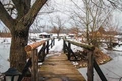 Small old wooden bridge on frozen lake royalty free stock photo