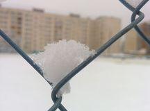 Snow on the metal grid. The snow on a metal grid. City in the background Royalty Free Stock Photo