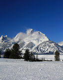 Snow mist blowing off Grand Tetons peaks  in front of snowfield in Grand Tetons National Park (GTNP) Stock Photography