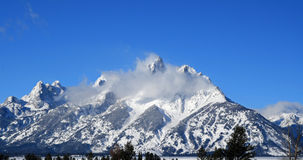 Snow mist blowing over Grand Tetons Mountain Range in Grand Tetons National Park (GTNP) in Wyoming Stock Photography