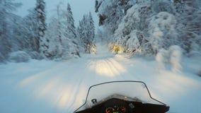 Snow mobile speeding through snowy forest stock footage