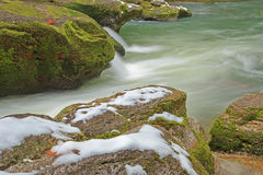 Snow on mossy rocks beside smooth cool flowing river water Royalty Free Stock Photos