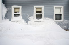 Snow mound under three windows. A huge snow mound piled under three residential windows in the aftermath of the Blizzard of 2013 in Worcester, Massachusetts Royalty Free Stock Photo