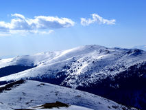 Snow Mountain.....(2). Here are some Mountains in Romanian country. They are full of snow. The sky is blue Stock Images