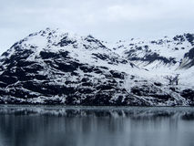 Snow Mountain along the Glacier Bay in a Cloudy and Calm Day Stock Image
