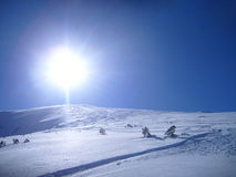 Snow mountain and big bright sun Stock Photography