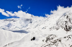 Snow mountain peak with clouds and blue sky Stock Images