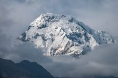 Snow Mountain Peak among Moving Clouds in the Himalayas in Nepal