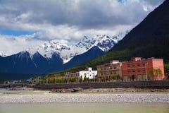 Snow mountain peak with village in Tibet Royalty Free Stock Photos