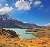 Snow mountain peaks and  lake with emerald water Stock Photos