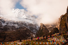 Snow Mountain with Prayer Flag in Sunrise Glory in Yubeng Stock Photo