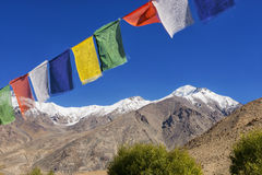 Snow mountain range and tibetan prayer flags in the village ,Leh-Nubra Valley Road Ladakh ,India - September 2014 Royalty Free Stock Image