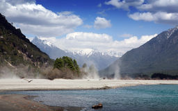 Snow mountain and river. Under snow mountain, sand on river bank blown by wind Stock Photos