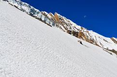 Snow mountain slope with rocks, glacier and blue sky with moon Royalty Free Stock Photography