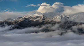Snow mountain tops in clouds. Dawn. Mount Mamkhurts. Royalty Free Stock Images