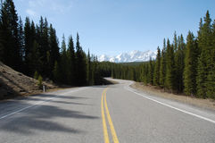 Snow mountain and winding highway. View of mountain peak and winding highway in kananaskis county, alberta, canada royalty free stock photography