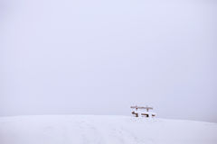 Snow mountain with wooden bench. Winter landscape Royalty Free Stock Photo
