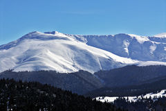 Snow and mountains. Snow and blue-cloudy sky mountain panorama Royalty Free Stock Image