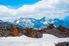 Snow on the mountains against the blue sky in the clouds.The Elbrus region.The Caucasus. Royalty Free Stock Photography