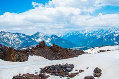 Snow on the mountains against the blue sky in the clouds.The Elbrus region.The Caucasus. Royalty Free Stock Photo