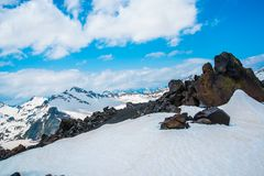 Snow on the mountains against the blue sky in the clouds.The Elbrus region.The Caucasus. Stock Photo
