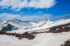 Snow on the mountains against the blue sky in the clouds.The Elbrus region.The Caucasus. Stock Images