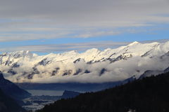 Snow mountains. low clouds ang the lake under clouds Royalty Free Stock Image