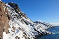 Snow on mountains near water Stock Photo