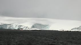 Snow mountains in ocean of Antarctica. Travel in calm and silence of cold polar north. Scenic blue water. Global warming. Unique nature of ice desert stock video footage