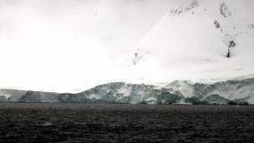 Snow mountains in ocean of Antarctica. Travel in cold polar north. Landscape of nature in ice desert . Wilderness area stock video footage